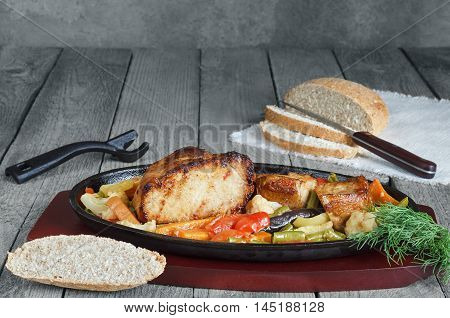 Fried pork with vegetables and herbs in a cast iron skillet and a wooden stand. Blue gray wood background, rustic style.