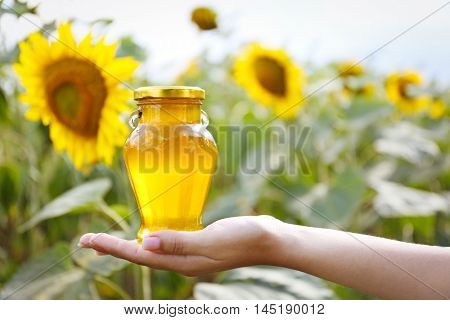 Woman holding bottle of honey on sunflower field background
