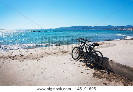 Two bikes parked on sandy beach near turquoise water and Mediterranean ocean in Palma de Mallorca Balearic islands Spain on April 10 2016.