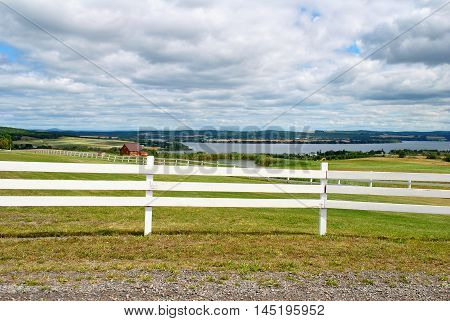 Close Up of a White Fence with a River and Farming Land in the Background