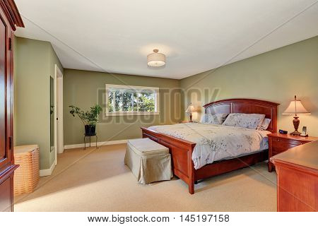 View Of King Size Wooden Bed In Olive Bedroom Interior.