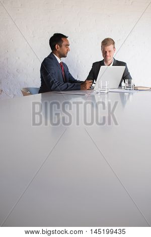 Two confident young businessmen in suits talking together over a laptop while sitting at the back of a large table in a modern boardroom