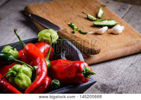 Colored pepper and garlic on cutting board.