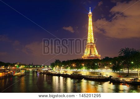 Paris, France - May 27, 2016: Famous  Eiffel tower and Seine river at night on May 27, 2016 in Paris. Eiffel Tower is a global cultural icon of France and one of the most recognisable structures in the world.