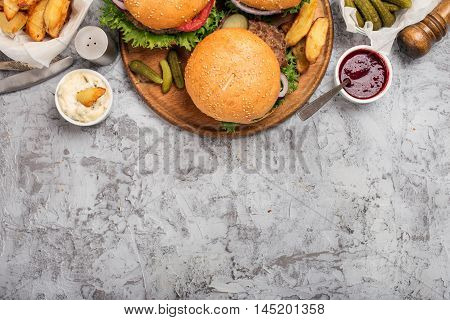 Burgers grilled on wooden round board on light rough surface with sauces and fries top view with copy space