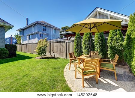 Small Patio Area With Wooden Table Set And Umbrella.