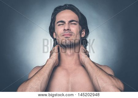 Feeling that awful pain. Portrait of young shirtless man keeping eyes closed and expressing negativity while touching his neck and standing against grey background