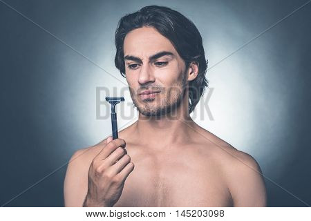Really bad razor. Portrait of thoughtful young shirtless man looking at razor while standing against grey background