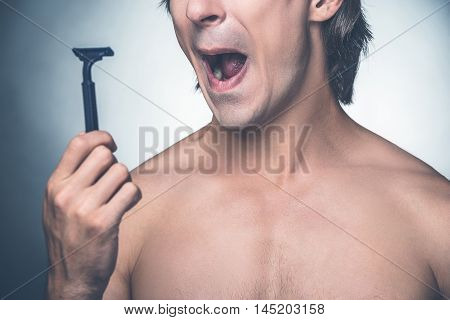 He needs a new razor. Close-up of young shirtless man holding razor and expressing negativity while standing against grey background
