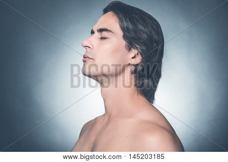 Fresh and clean. Side view of young shirtless man keeping eyes closed and looking calm while standing against grey background