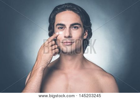 Making his face fresh and clean. Portrait of handsome young shirtless man applying moisturizer on face and looking at camera while standing against grey background