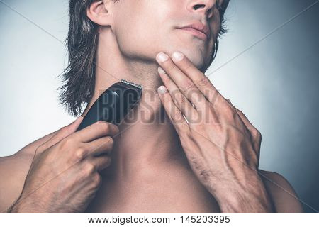 Shaving with electric razor. Close-up of handsome young shirtless man shaving with electric razor while standing against grey background