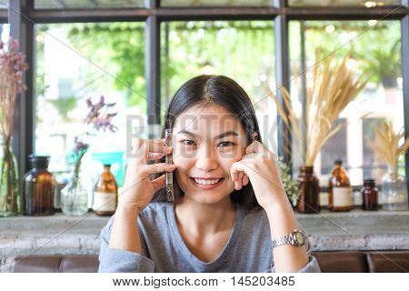 Beautiful Asian Young Woman Using Cell Phone While Sitting At Cozy Art Coffe Shop