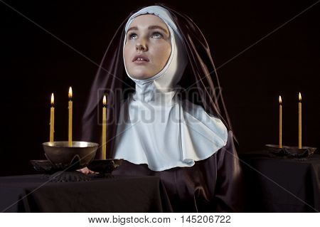Young catholic nun through the candles. Photo on black background. Low key lighting.
