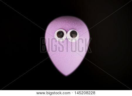 Make up - sponge egg with googly eyes. isolated on black background.
