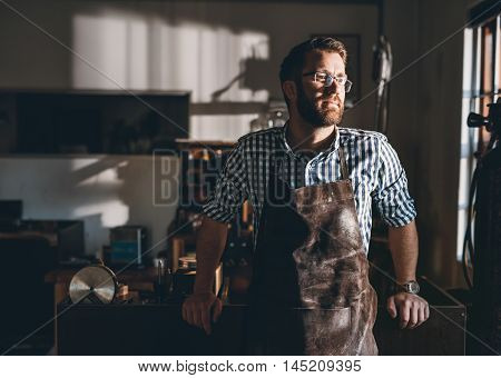 Young jeweler in an apron  standing in his workshop looking through the window of his workshop  in the afternoon