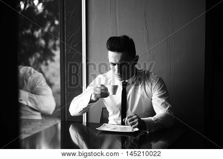 Man young handsome elegant model wears shirt skinny necktie sits at table drinks coffee reflects in glass window and looks in cup indoor black and white on grey background