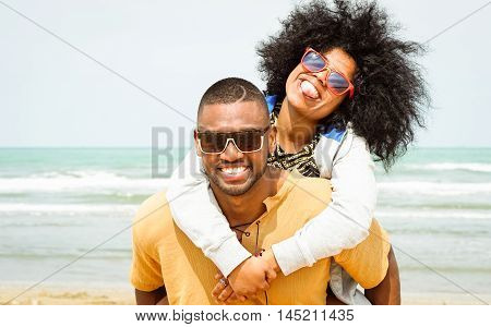 Young afro american couple playing piggyback ride on beach - Cheerful african friends having fun at day with blue ocean background - Concept of lovers happy moments on summer holiday - Vintage filter poster