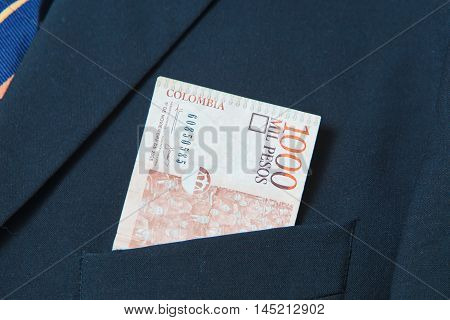 Colombian Pesos in the pocket of a suit