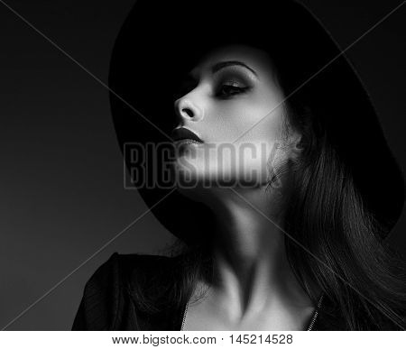 Elegant Sexy Makeup Woman Profile Posing In Fashion Hat On Dark Background. Closeup Black And White