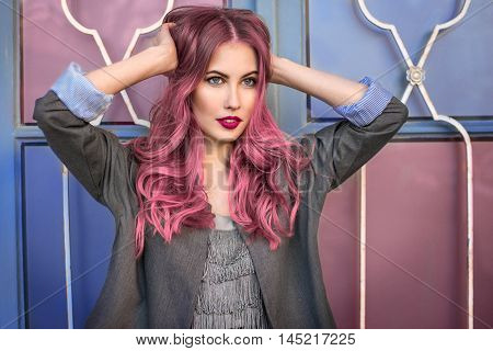 Beautiful hipster fashion model with curly pink hair posing in front of the colorful wall