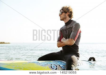Smiling young male surfer sitting on his surf board with hands crossed in ocean wearing swimsuit