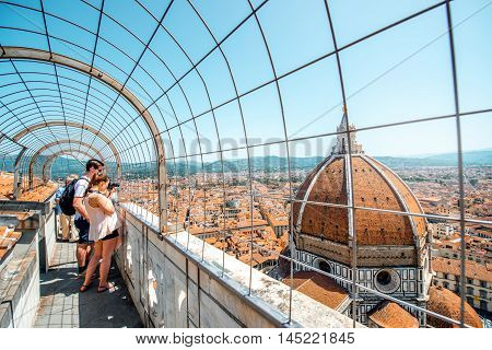 Florence, Italy - May 26, 2016: Tourists enjoy great view on Santa Maria Del Fiore cathedral from the bell tower in Florence