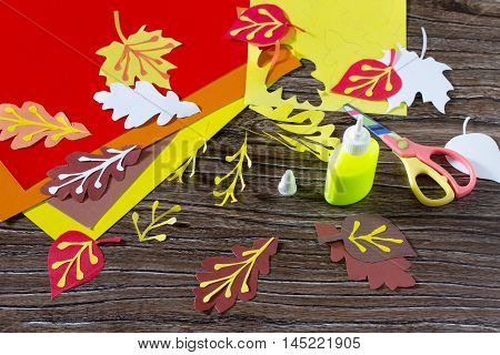 Autumn Colored Paper Leaves On The Wooden Background. Child Be Glued Paper Leaves. Sheets Of Paper C