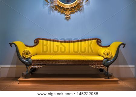 Luxury yellow sofa in front of the blue wall