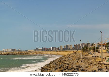 Cityscape scene depicting the coastline and beach surrounded by modern modern buildings in Fortaleza Brazil