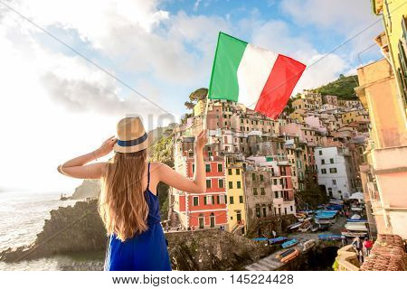 Young female traveler with italian flag enjoying great view on the old coastal town in Riomaggiore on the northern Italy. Promoting tourism in Italy