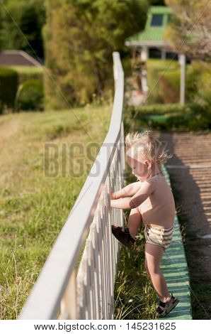 baby boy tries to climb over the fence