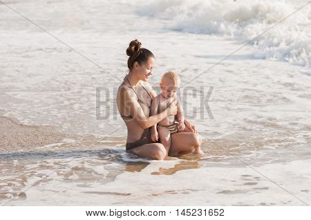 mother and child sitting on the coast waiting for a wave