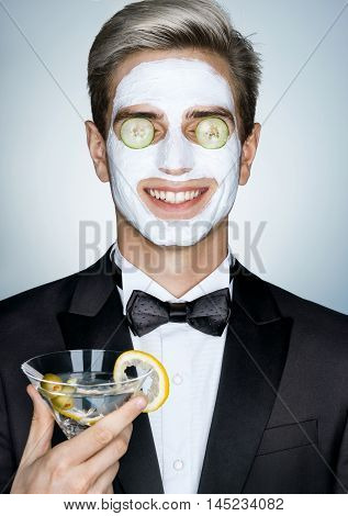 Relax. Gentleman with glass of martini and cosmetic mask on the face. Photo of happy stylish man receives the spa treatments. Grooming himself