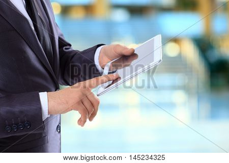 Businessman with the tablet  on the background of the office