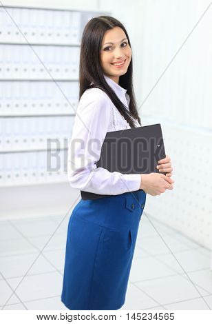 portrait of a beautiful young woman administrator on the background of bright office