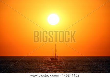 Beautiful gold and orange sundown with a sailboat sailing on a calm sea