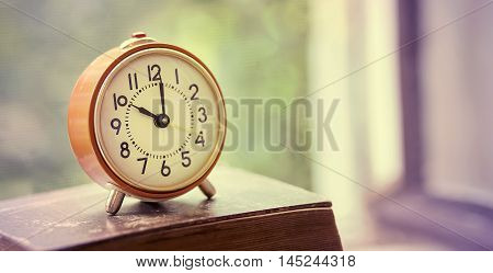 Website banner of a retro alarm clock on an old book