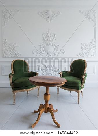 Luxury clean bright white interior with a old antique vintage green chairs over wall design bas-relief stucco mouldings roccoco elements.