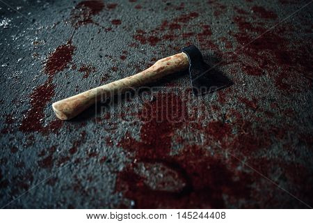 Bloody ax of maniac lying on the floor