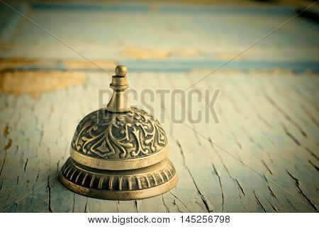 Old service bell resting on weathered wooden surface with blue peeling paint blended with a textured background for a painterly feeling.