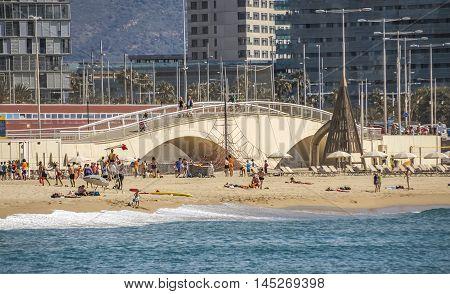 BARCELONA SPAIN - JULY 13 2016: Beach and pedestrian bridge at Sant Marti district Barcelona Spain