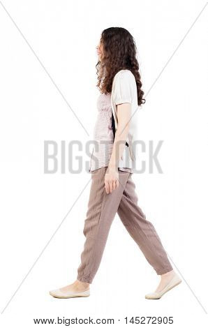 back view of walking  woman.  backside view of person.  Rear view people collection. Isolated over white background. Girl in brown trousers goes to the right