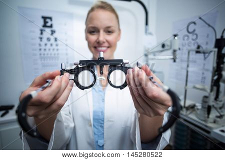 Portrait of smiling female optometrist holding messbrille in ophthalmology clinic