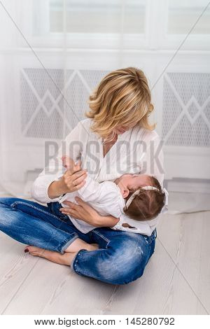 Young mom breastfeeding her child baby girl lying on her breast and feeding on a whine background