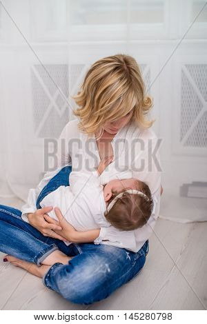 Happy mom breastfeeding her child baby girl lying on her breast and feeding on a whine background