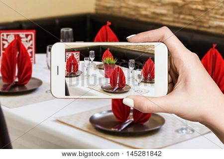 Woman photographing on smartphone, interior of a modern restaurant, table set