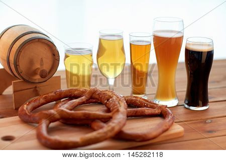 brewery, drinks and food concept - close up of different beer glasses, wooden barrel and pretzels on table