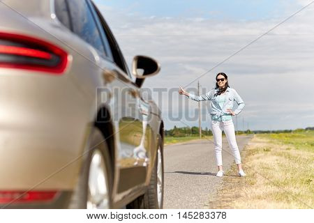 road trip, hitchhike, travel, gesture and people concept - woman hitchhiking and stopping car with thumbs up gesture at countryside road