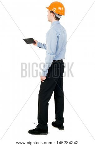 Backview of business man in construction helmet stands and enjoys tablet or using a mobile phone. Curly businessman in a light jacket and a helmet reads works with the tablet on the site.